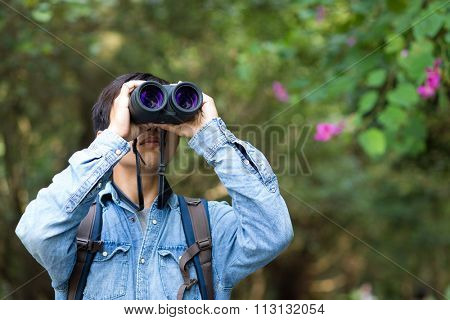 Young Man watching though binoculars