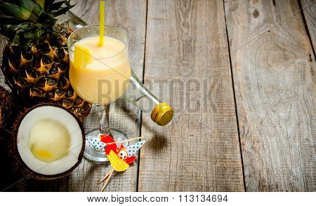 Fresh Cocktail In The Glass, Rum, Coconut And Pineapple On A Wooden Table. Free Space For Text.