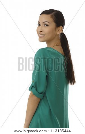 Attractive young woman looking over shoulder, smiling in green blouse.