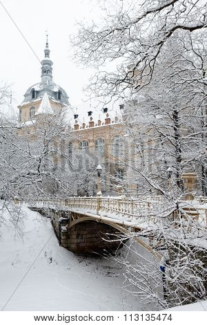 Snow covered mansion and bridge at empty winter park outdoor. Vintage yellow building, trees.