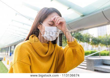 Woman got serious headache and wear face mask