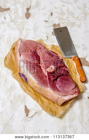 A Piece Of Raw Meat With A Butcher Knife On The Paper.
