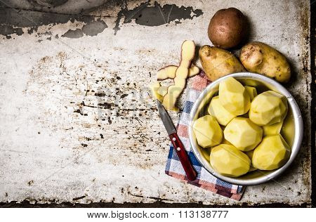 The Peeled Potatoes In A Metal Bowl On The Rustic Background . Free Space For Text.