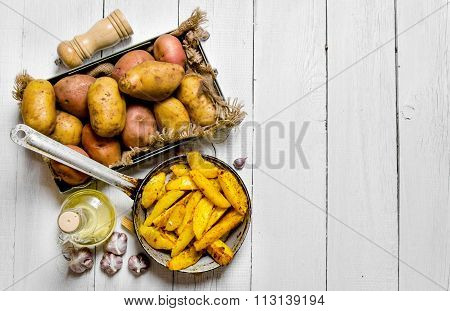 The Concept Of Baked Potatoes In A Skillet With Spices On A White Wooden Table. Free Space For Text.