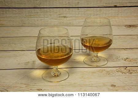 Two Glasses Of Cognac On A Wooden Countertop