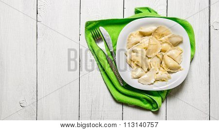 Fresh Ravioli With Cheese In The Plate. On White Wooden Background.