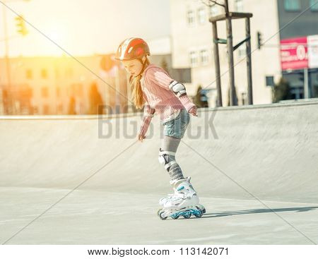 Little cute girl on roller skates in helmet at a park