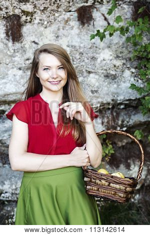 Young woman with basket filled with apples