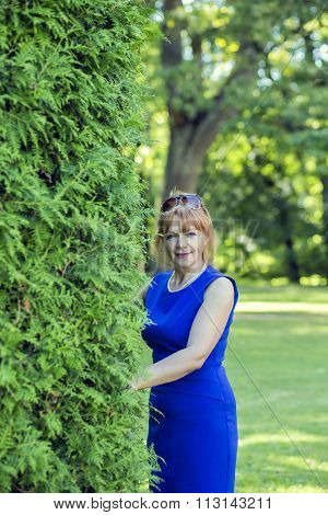 Graceful adult woman peeking from the bushes