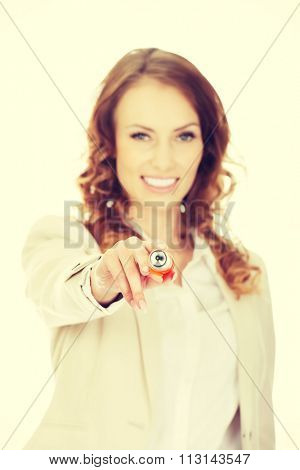 Attractive businesswoman pointing on camera with oversized pen.