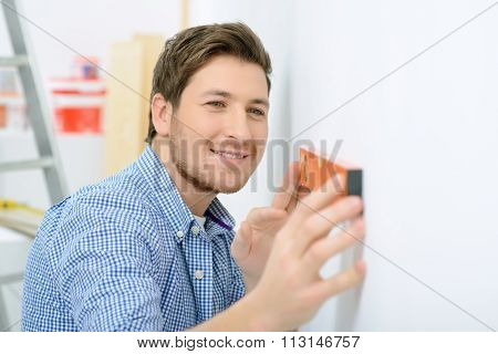 Cheerful father holding spirit level