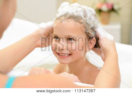 Cute little girl washing her hair