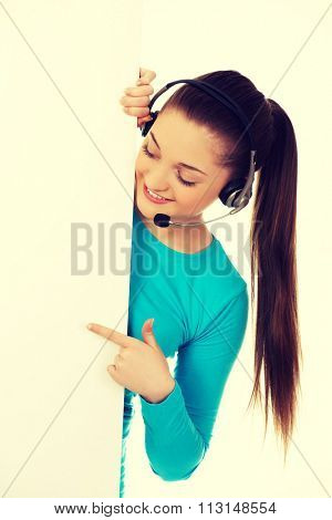 Young call center woman pointing on billboard.