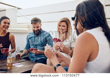Young People Playing A Game Of Cards During A Party
