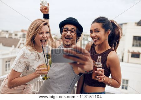 Friends Taking A Selfie On Rooftop Party