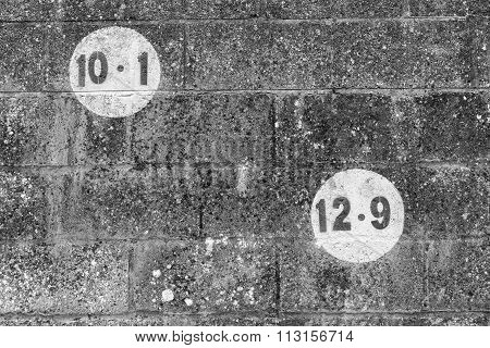A Black And White Photo Of Numbers In A Circle Painted On Dark Brickwork Wall In The Outdoors