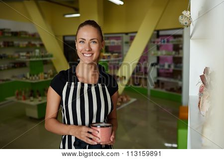 Cheerful female entrepreneur posing during work day on her cosmetics shop