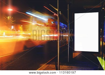 Clear public information board in night city with cars's movement on background, bus stop lightbox