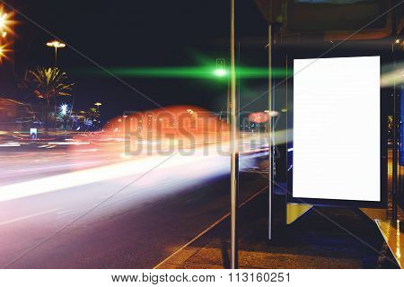 Public information board with blurred cars lights on background