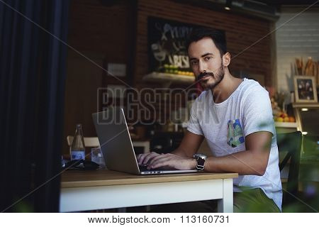 Handsome man freelancer working on net-book while sitting in modern coffee shop indoors