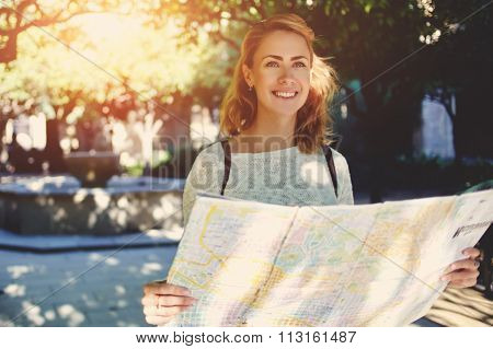 Beautiful happy female tourist exploring location map before touring in a city during her travel