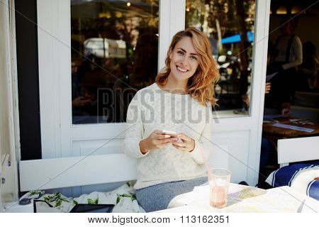 Happy hipster girl writing text messaging on cell telephone during recreation time in coffee shop
