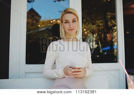 Young attractive woman holding mobile phone in hands while sitting in modern coffee shop
