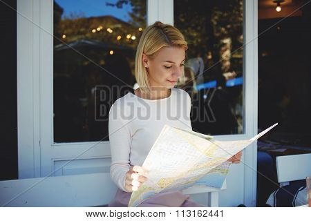 Charming hipster girl examines geographical atlas while sitting in modern sidewalk cafe in summer