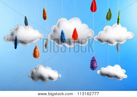 Fleece clouds with raindrops on blue background