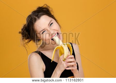 Portrait of funny beautiful young woman eating banana over yellow background