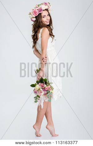 Full length of beautiful smiling young woman in white dress and wreath of roses standing barefoot with bouquet of flowers
