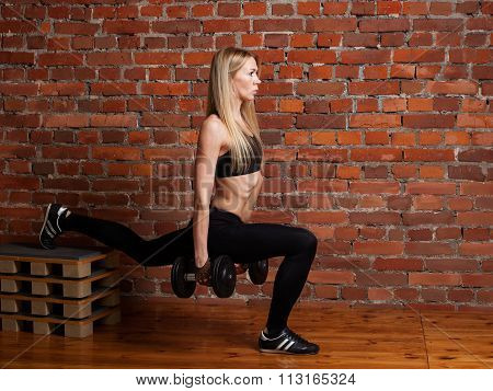 Young Fitness Model Performing Lunges With Dumbbells On The Box
