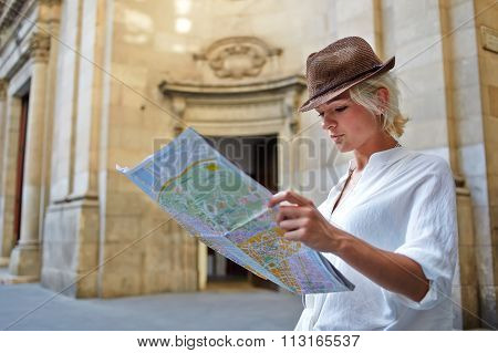 Young female student with trendy look examines atlas during traveling abroad in summer vacation