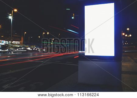 Public information board in night city with beautiful lights on background,  advertising mock up