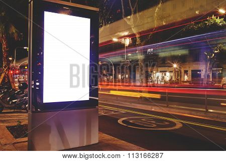 Public information board in night city with blurred movement of cars on background