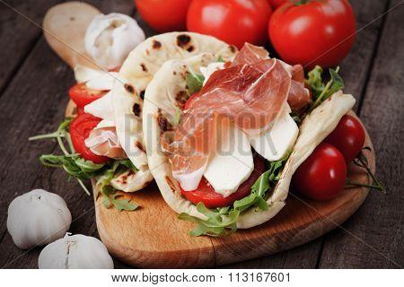Piadina romagnola, italian flatbread sandwich wth prosciutto and mozzarella cheese