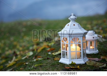 Lanterns with candles on grass, on mountains background