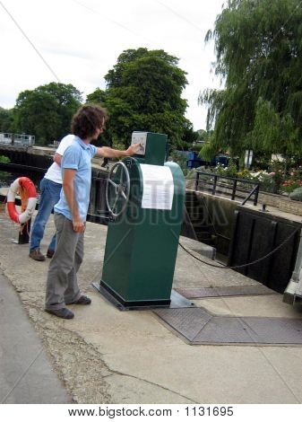 Lock Keeper Openning The Lock Gates Of Canal. Working.