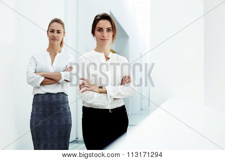 Prosperous businesswomen with confident look posing in hallway company