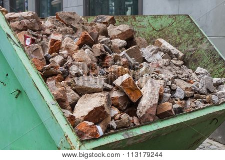 Debris in a green metal container. Broken bricks from the demolition of the building.