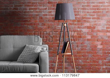 Comfortable sofa and lamp on brick wall background