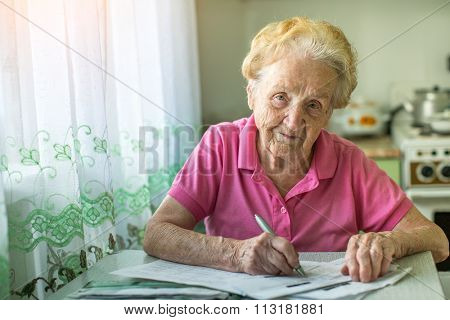 An elderly woman fills the bill for payment of utility services.