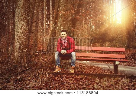 Smiling Man Sitting On Bank In The Autumn Season And Enjoy The Scenery