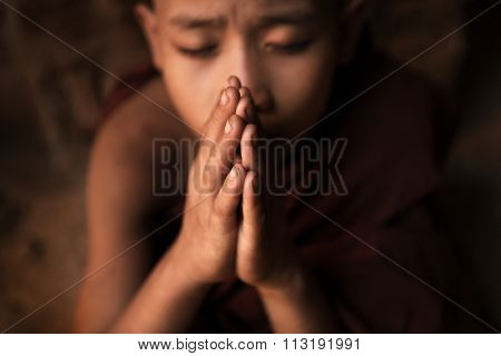 Young novice monk praying inside Buddhist temple, low light with noise setting, Bagan, Myanmar.