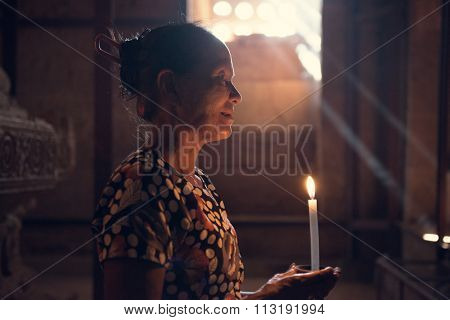Old wrinkled traditional Asian burmese woman praying with candle light inside a temple, low light, Myanmar