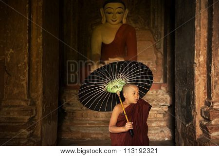 Portrait of young novice monks with umbrella inside ancient Buddhist temple, Bagan, Myanmar.