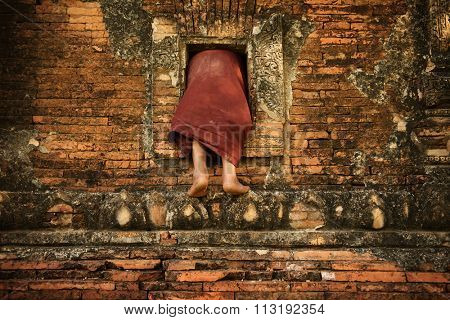 Young novice monks climbing into Buddhist temple from window, Bagan, Myanmar.
