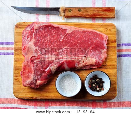 Raw juicy T-Bone beef steak on a wooden board with salt, pepper and a knife