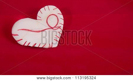 The Heart Which Is Cut Out From Paper And Sewed By A Red Thread On A Red Velvet