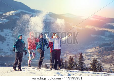 Young happy friends having fun in winter mountains